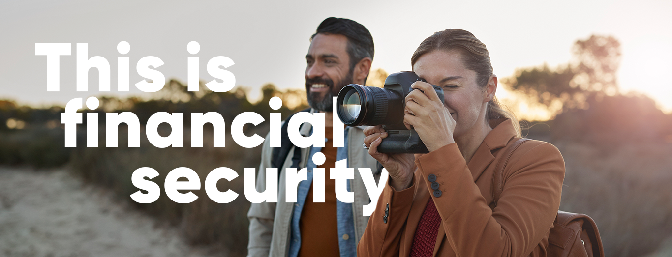 This is financial security; photo of two people smiling in nature, one is holding a camera and taking a photo.